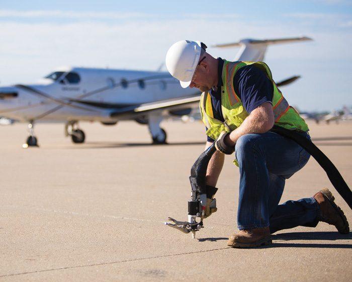 Workman Inserting Foam to Lift Concrete Slab